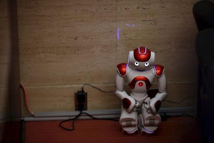 "A ""Nao"" humanoid robot by Aldebaran Robotics sits in a corner while its batteries are being charged during a presentation at a branch of the Bank of Tokyo-Mitsubishi UFJ (MUFG) in Tokyo in this April 13, 2015 file photo. Three-fourths of robot installations over the next decade are expected to be concentrated in four areas: transportation equipment, including the automotive sector; computer and electronic products; electrical equipment and machinery. Labor costs have climbed in countries such as China that have been popular for outsourcing production, while technological advances for robots allow them to be more flexible and perform more tasks. REUTERS/Thomas Peter/Files ATTENTION EDITORS - THIS PICTURE IS PART OF THE PACKAGE ""RISE OF THE MACHINES"". TO FIND ALL 20 IMAGES SEARCH 'TECHNOLOGY ROBOTS'.      TPX IMAGES OF THE DAY"